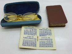 A 1946 calendar, an English to Latin book and a case with children's spectacles, c.1940