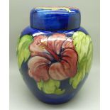 A Moorcroft hibiscus ginger jar on blue ground, signed, with paper label inside lid, 20cm