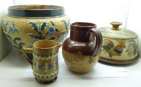 A Doulton Lambeth jardiniere, two relief moulded jugs and a saltglaze cheese dish and cover,