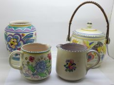Four items of Poole pottery; a biscuit barrel, vase and two jugs, one jug crazed
