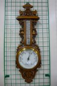 An early 20th Century carved oak aneroid barometer, 88cms h