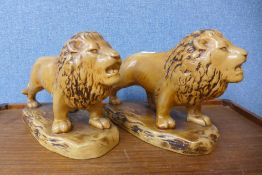 A pair of Staffordshire pottery lions, impressed mark to base; Made In England, 822, 21cms h