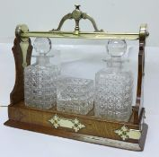 An oak framed tantalus, marked Fenton Bros., Sheffield, and Staniforth Patent, glass a/f