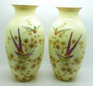A pair of Edwardian Crown Ducal blush ivory vases decorated with birds and butterflies, 24.5cm