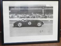 A large framed black and white print of Sir Stirling Moss in the 1953 Jaguar 'C', signed, 32.5 x