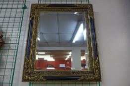 An ebonised and parcel gilt framed mirror