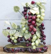 An Asian art centrepiece, jade grapes and carved soapstone vine leaves with carved wooden base, 39cm