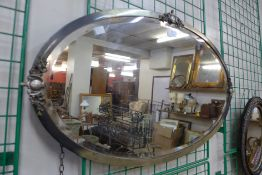 An Art Deco burnished steel oval mirror