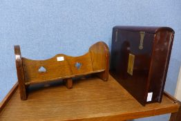 An Arts and Crafts oak book trough and a hardwood and brass mounted book shaped folio box