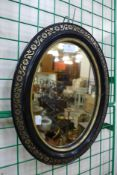 A small Victorian ebonised and parcel gilt framed oval mirror