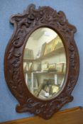 A carved oak oval framed mirror, 72 x 50cms