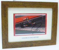 A framed photograph of a McLaren F1 car, signed by Lewis Hamilton