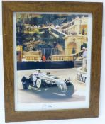 A framed photograph of Sir Stirling Moss with mounted autograph