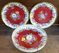 A pair of German decorative plates and a similar shallow bowl