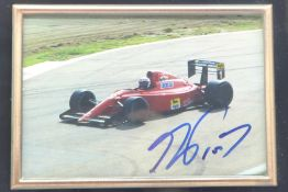 A framed photograph of a Ferrari F1 car, signed by Alain Prost