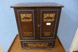 An oak table top cabinet, bearing Sunlight Soap inscription to doors