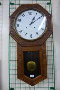A carved oak wall clock