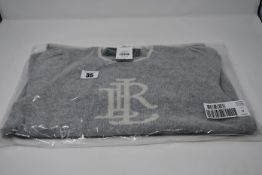 An as new Ralph Lauren 3/4 sleeve grey/cream sweater with with motif to front (Size M).