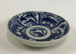 A Japanese Kozara porcelain blue and white plate, Seigaiha pattern, marks to base, 11cmD