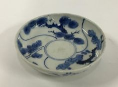 A small Japanese porcelain plate, blue and white with lucky charm plant and bamboo design, marks