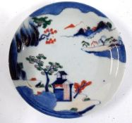A Japanese porcelain plate, decorated sansui mountain scenery, in blue, green and red, heightened in