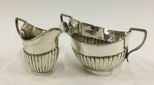 A half gadrooned silver milk jug and sugar bowl by Thomas Hayes, Birmingham 1898, 5oz