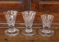 Three Masonic glasses, of tapering form, etched with symbols and raised on circular spread feet,