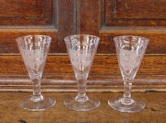 Three Masonic etched wine glasses, having shield motifs, raised on circular spread bases, some