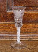 An Antique drinking glass, the bell shaped bowl etched with flowers and butterflies, supported on