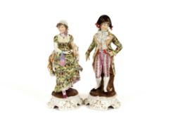 A pair of 19th Century German porcelain figures, of a lady and gallant, wearing brightly coloured