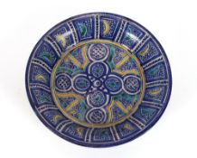 A 19th century Iznik style bowl, predominately in blue heightened with yellow and green within a