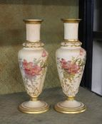 A pair of late 19th Century Royal Worcester vases, decorated floral sprays heightened in gilt on a