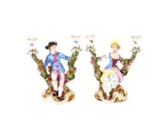 A pair of 19th Century Meissen porcelain figural candlesticks, depicting maid and youth seated on