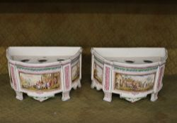 A pair of 19th Century French porcelain bough pots, of demi lune shape, the panels decorated with