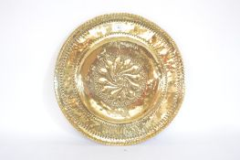 A large Antique brass alms dish, 21ins dia. approx.