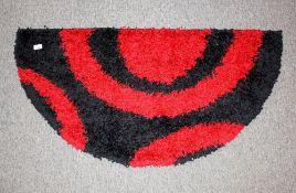 A 1960's / 70's design woollen hearth rug of semi-