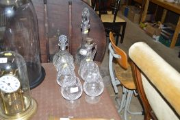 Five glass brandy balloons, two decanters each wit