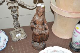 A carved wooden figure group on the form of a maid
