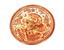 A Hispano Moresque earthenware deep charger, having pink lustre decoration of a mythical bird and