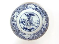 A Delft blue and white charger, decorated with a central scenic panel of a boy and shepherdess,