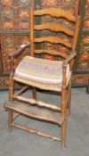 An antique elm child's ladder back high chair, rush seat above foot rest on turned supports united