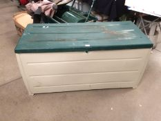 A beige moulded plastic garden storage box with green top 120 x 64 x 50cm high - manufacturer Keter