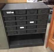 A black metal twenty drawer stores cabinet with under storage area - 85 x 40 x 100cm