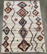 A cream and multi coloured diamond patterned rug - 160cm x 230cm