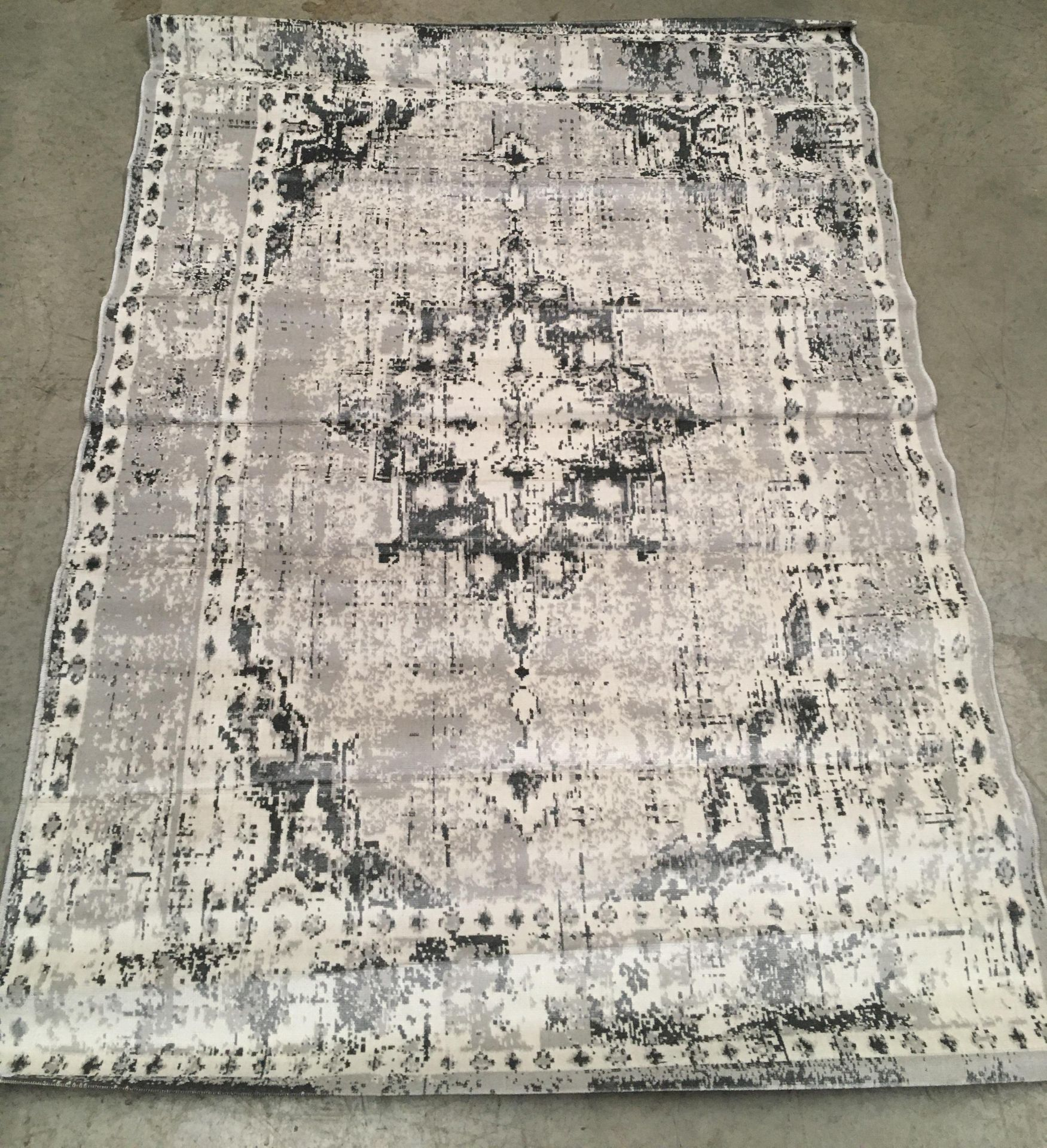 Lot 23 - A modern grey and beige faded patterned short pile rug - 220cm x 160cm