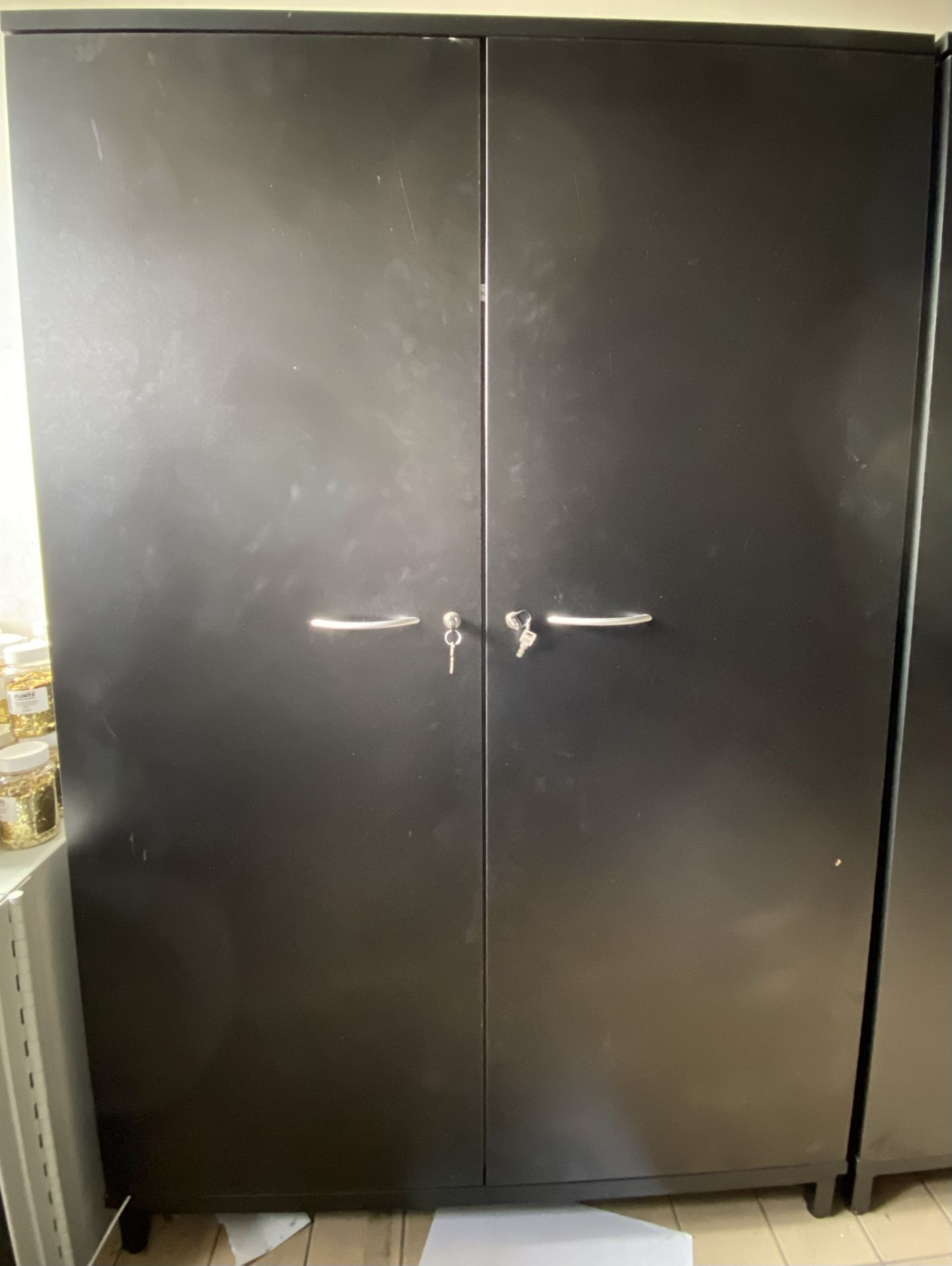 A black 2 door wooden stationary cabinet
