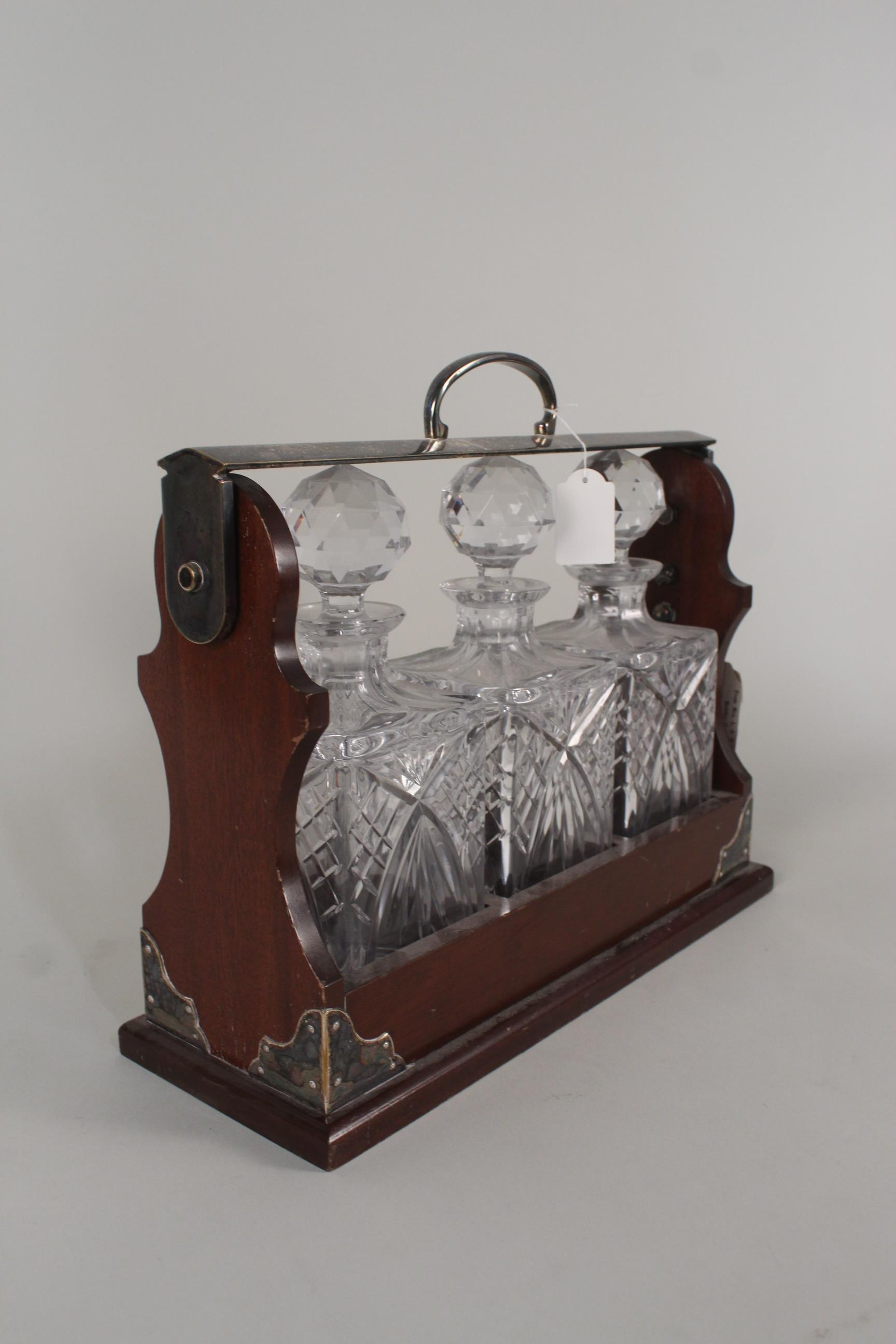 Lot 706 - An oak and silver plated three cut glass decanter tantalus, marked PB&S with key,