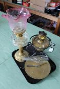 A brass base oil lamp with clear glass reserve shade (as found) together with a cast and brass base
