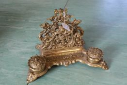 "An ornate vintage double brass ink stand, marked ""Brevettato"" to base, decorated with cherubs,"