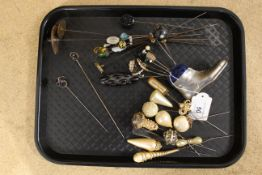 A selection of hat pins in a pewter 'boot' hat pin holder including two silver examples